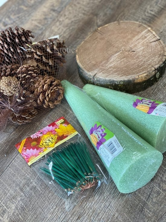 materials of foam floral cone wood slab, pinecones and floral picks needed to create a diy pinecone tree.