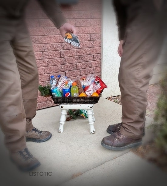 UPS delivery drivers picking out a snack from a goodie basket left outside the door for them