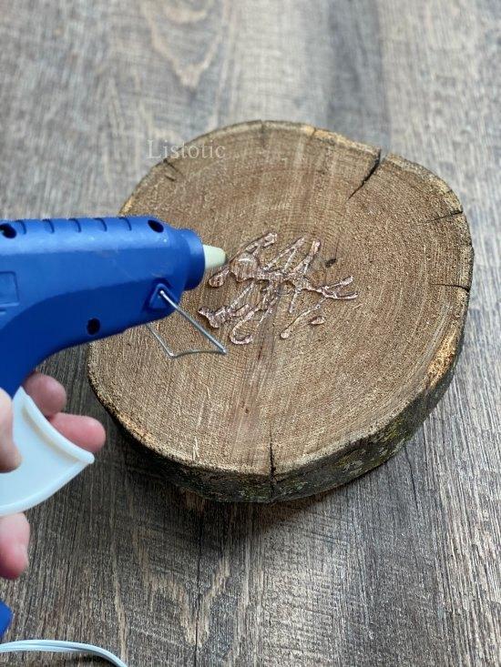 Wood slab with hot glue gun person applying hot glue
