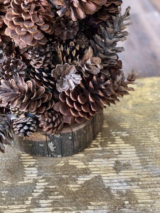 base of a diy pine cone tree craft resting on metallic corrugated cardboard