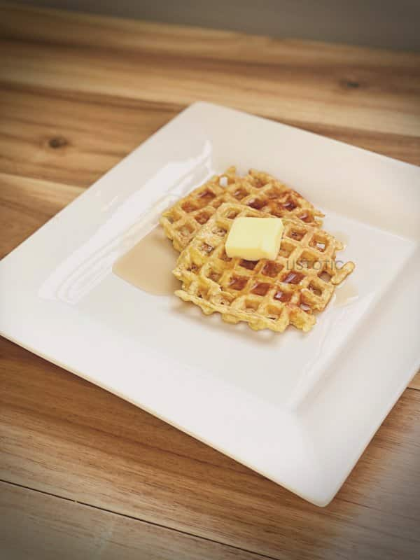 keto waffles on a white plate with butter and syrup