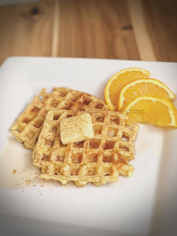 keto waffles covered in syrup, cinnamon and butter with orange sizes on a white breakfast plate