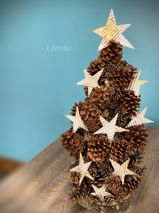 Rustic DIY pinecone Christmas tree with cardboard stars ornaments sitting on a table top