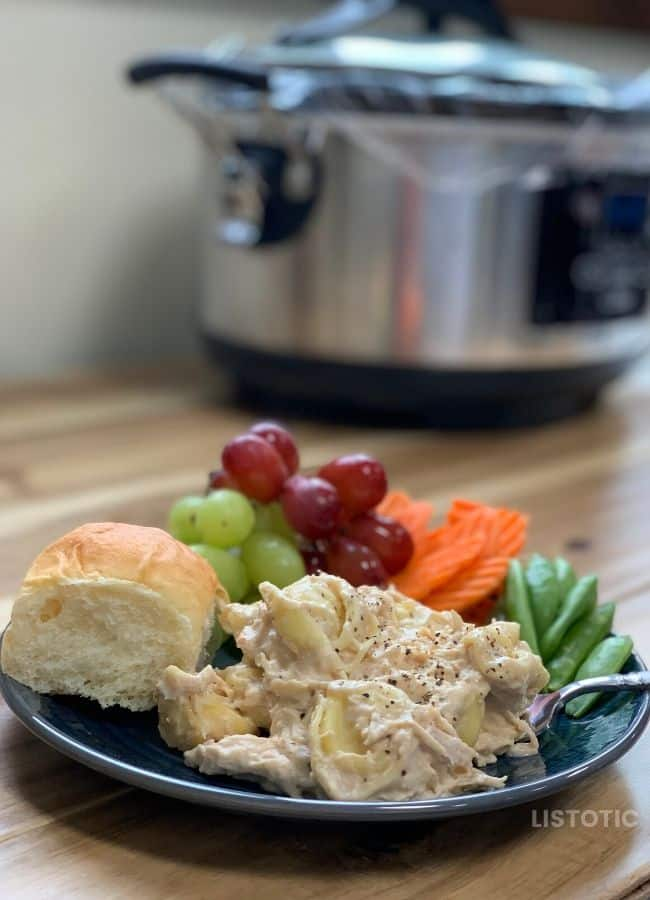 plate of chicken Alfredo with healthy fruits and veggies on a table in front of a slow cooker