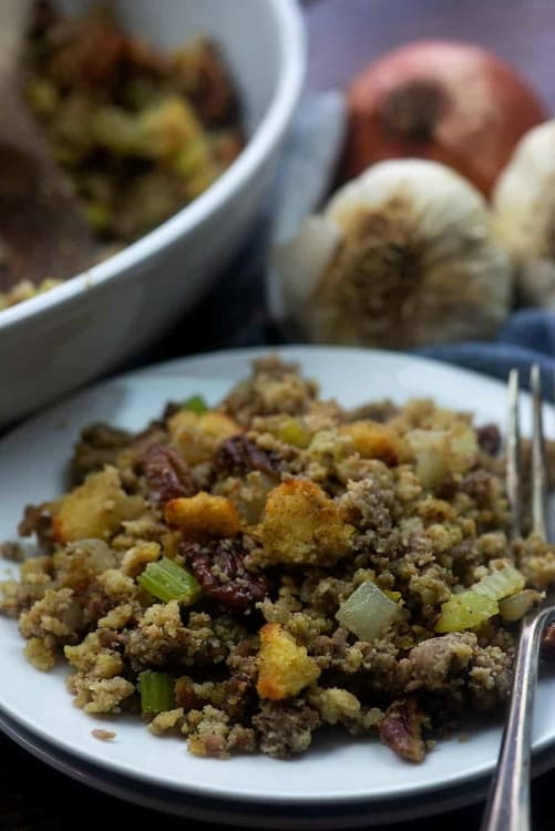 A plate with low carb cornbread, sage sausage, diced onion, diced celery and pecans.
