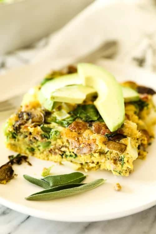 Keto friendly egg breakfast casserole slice topped with sliced avocado and sage leaves.