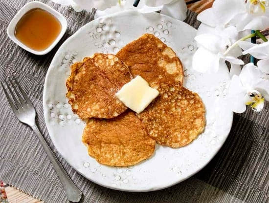 Four Small browned pancakes on a white plate topped with melting butter and a side of syrup.