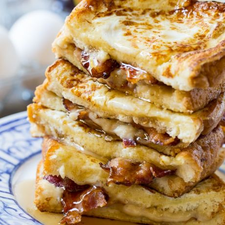 A stack of bacon stuffed french toast on a plate topped with syrup.