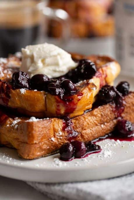 Blueberry cream cheese french toast on a plate topped with blueberries.