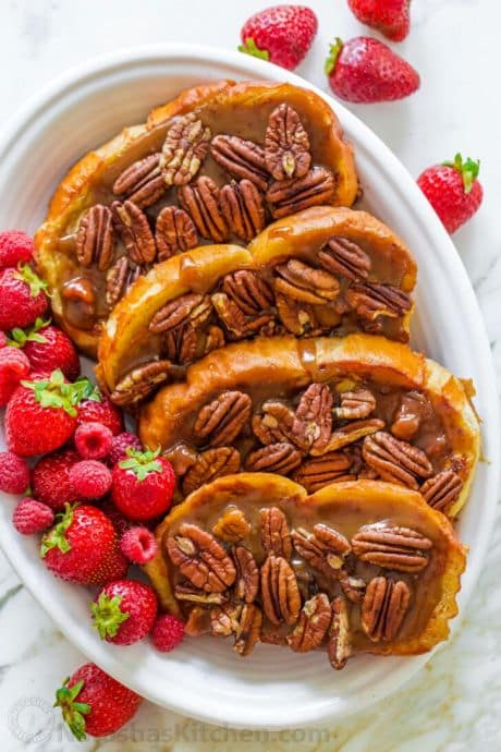Caramel french toast on a plate topped with pecans and berries.