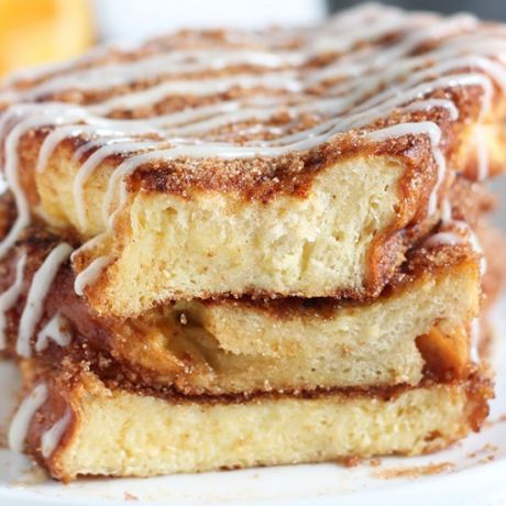 A stack of churro french toast coated in cream cheese drizzle on a plate.