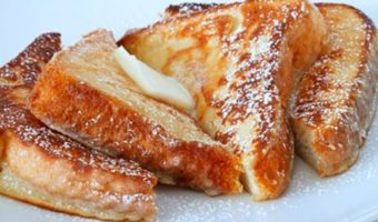Country style french toast coated with powdered sugar, butter, and syrup on a plate.