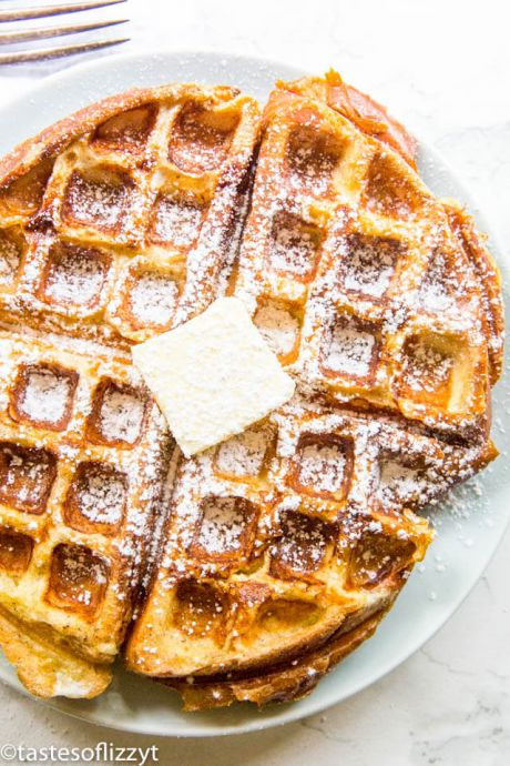 French toast waffle on a plate topped with butter and powdered sugar.
