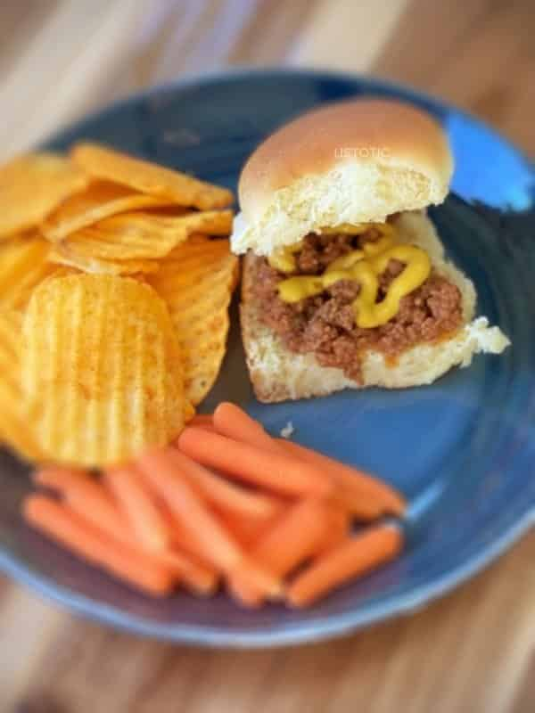 Loose meat sandwich with mustard on a blue plate with sides of carrots and chips