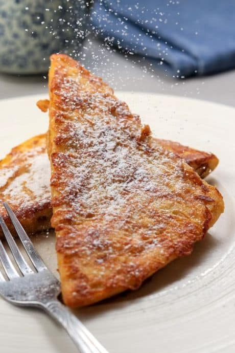 Keto-friendly french toast on a plate topped with powdered sugar.