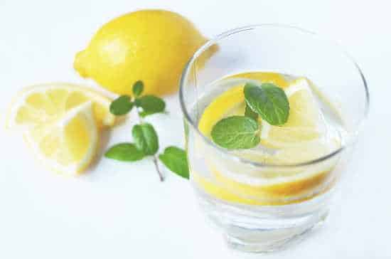 A glass of water with quartered lemon wedges and sprig of herbs.