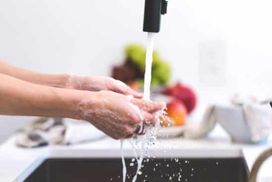 A person washing food or hands under running water in a kitchen with blurred background.