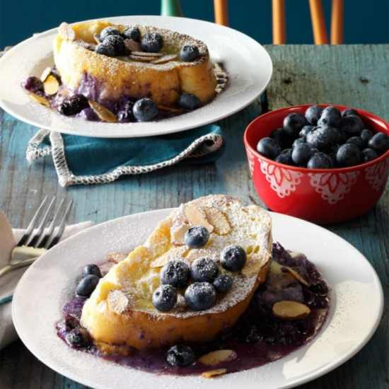 A slice of bread topped with blueberries and blueberry jam on a white plate.