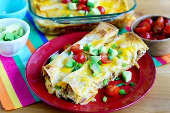 Loaded Breakfast enchiladas filled with pinto beans, hash browns, green chiles, bacon, eggs and topped with cheese, guacamole, tomatoes and diced avocado.