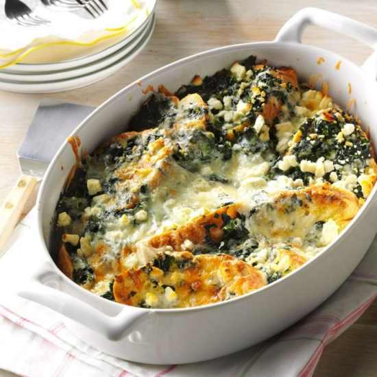 White casserole dish with browned creamy, melty feta cheese and spinach.