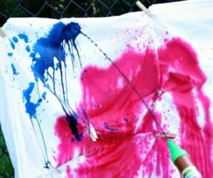 A water shooter spraying dye at a white piece of cloth.