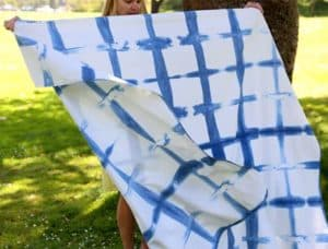 Woman holding an indigo tie dyed blanket while it blows in the wind.