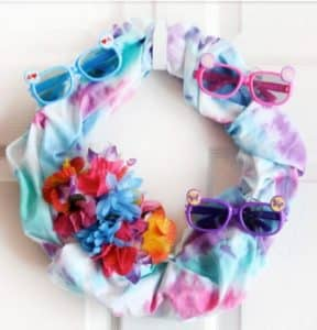 A tie dye wreath hanging on a wall, with colorful plastic sunglasses and faux flowers glued to the sides.