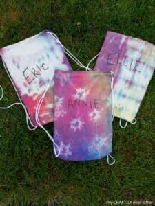 Three tie dyed drawstring bags next to each other laying on the grass.