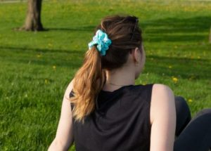 A woman sitting on the grass with her back towards the camera wearing a blue tie dyed scrunchie in her hair.