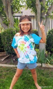 A young girl wearing a tie dye t-shirt.
