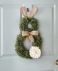 A bunny wreath hung on the face of a door.