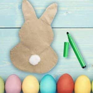 A customizable bunny yard flag on a table with a green marker and colorful Easter eggs placed beside it.
