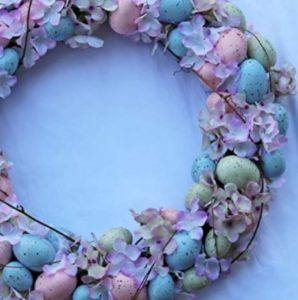 A wreath laced with brightly colored flowers and eggs sat on a light blue surface.