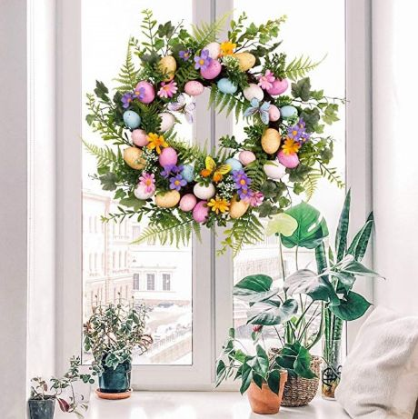 A colorful egg wreath hanging on a window.