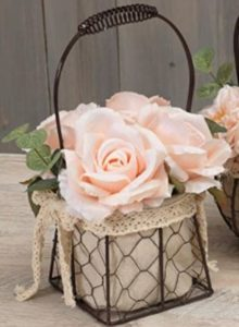 A wired basket lined with cloth and lace with light pink roses inside.