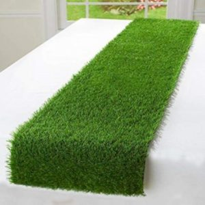 An artificial grass table runner displayed on a white table.