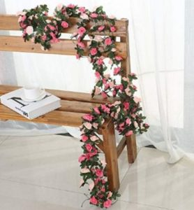 A faux rose garland entwined around the back and arm of a wooden bench.