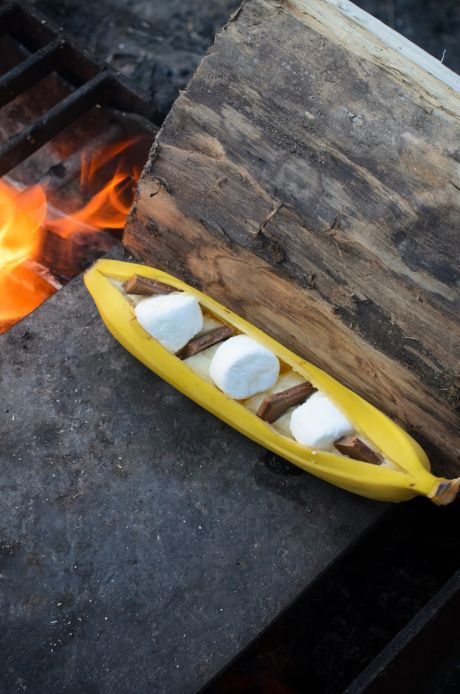 A campfire banana boat chocolate caramel s'more next to a bonfire.