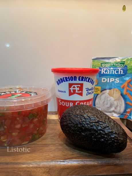An ingrediend lineup consisting of fresh salsa, sour cream, an avocado, and a packet of dry ranch.