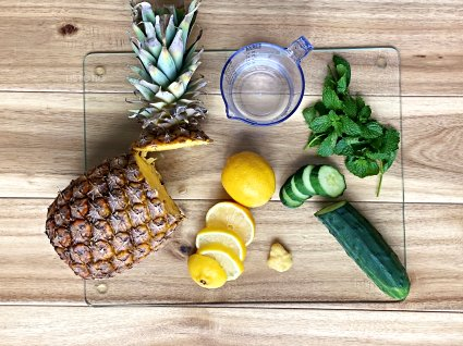 Fat burning drink ingredients of pineapple lemon, mint and cucumber on a cutting board