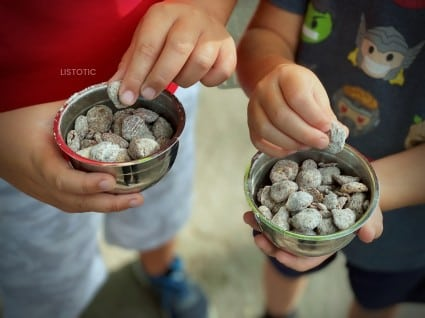 Kids hands picking up pieces of a peanut butter snack mix puppy chow recipe out of a small metal snack bowl