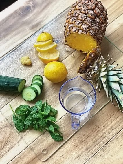 Pineapple, lemon, cucumber, mint chopped up on a cutting board for a detox drink