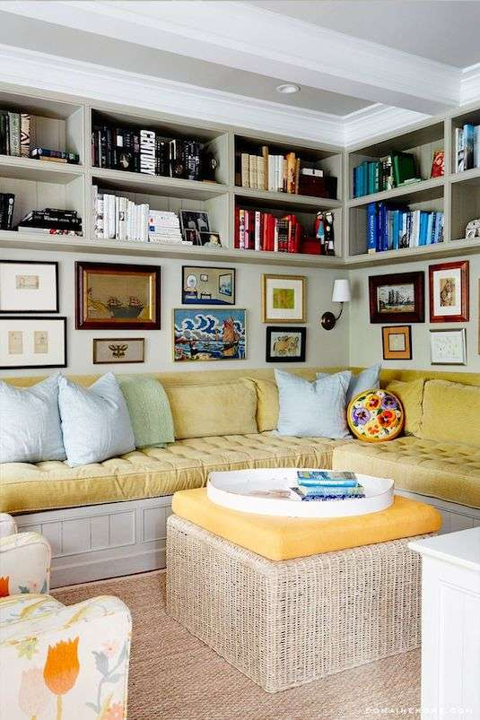 Tall bookshelves make great small space hacks. Image of a living room with book shelves to the celling