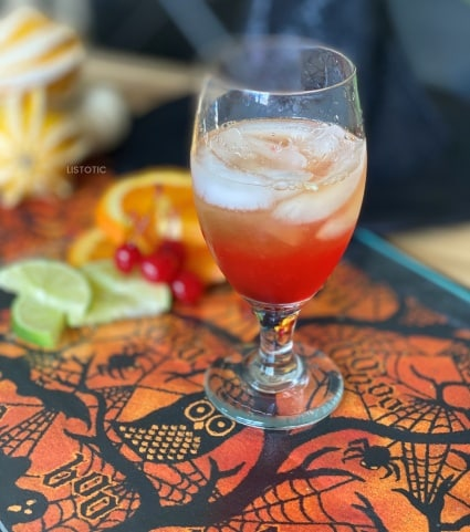 glass with ice orange juice alcohol and grenadine