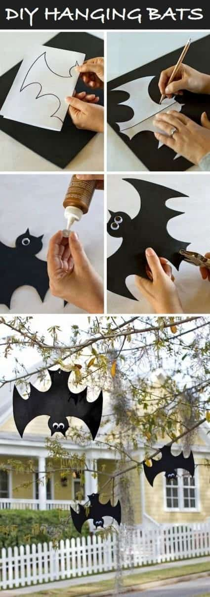DIY hanging bats. Cut out paper bats attached to tree branches for homemade Halloween decorations.