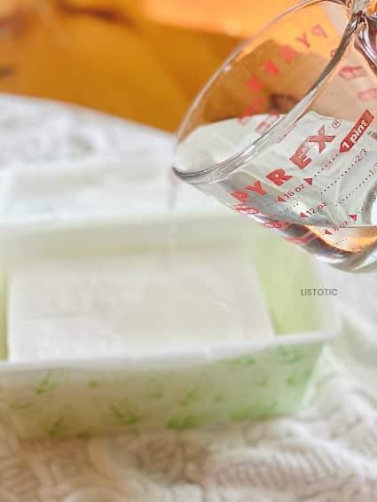 Messbecher gießt hausgemachte Desinfektionstücher Lösung über Babytücher
