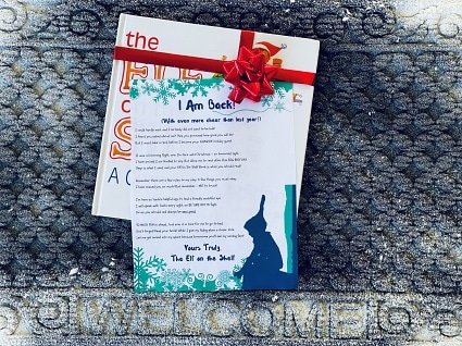 friendly arrival letter laying on the front door welcome rug with the Elf on the Shelf book