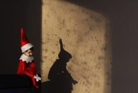 Christmas elf is back and he is sitting on the corner of the tv with his shadow showing on the wall behind him from the morning sun