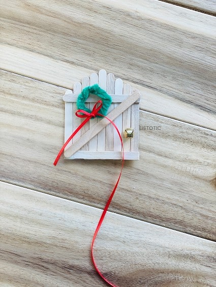 thin red ribbon tied in a bow around the diy miniature holiday wreath