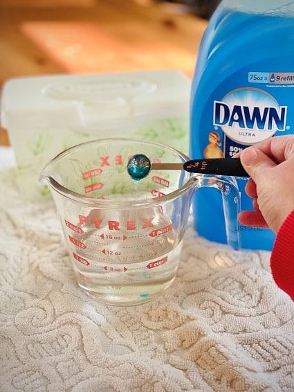 Dawn Spülmittel wird in einen Messbecher mit Alkohol für Küchentücher gegeben
